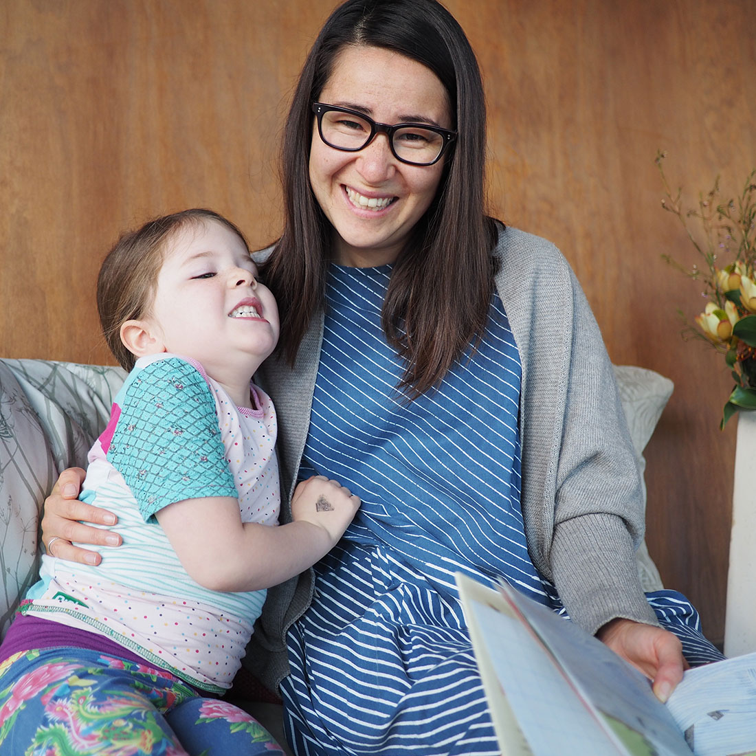Miyo Fallshaw on the couch reading a book to her daughter