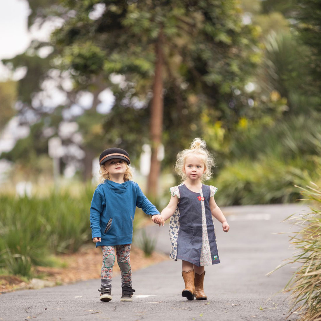 A three to four year old boy and girl model Oishi-m clothing while walking down a path in a park holding hands.