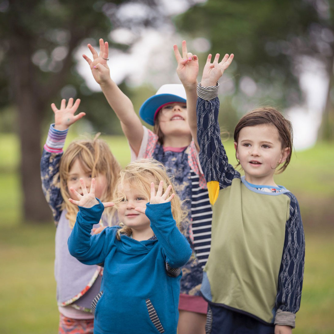 Four young children, under the age of five, raise their hands in the air while modelling a selection of Oishi-m clothing outdoors.
